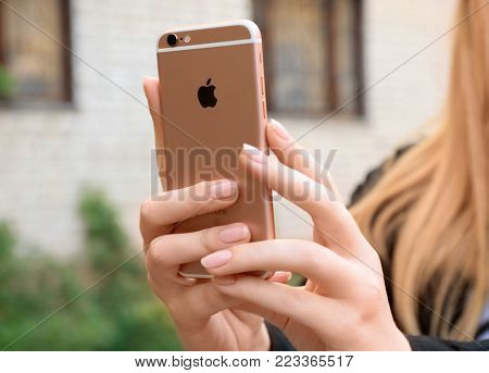 KYIV, UKRAINE - OCTOBER 17, 2017: Woman holding iPhone 6S Rose Gold outdoors