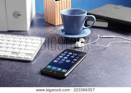 KYIV, UKRAINE - NOVEMBER 15, 2017: Apple iPhone 8 Space Gray with home screen on table