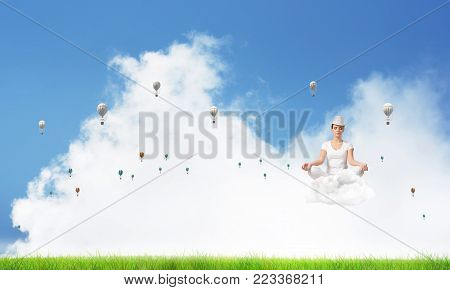 Young woman keeping eyes closed and looking concentrated while meditating on cloud among flying aerostats with bright and beautiful landscape on background.