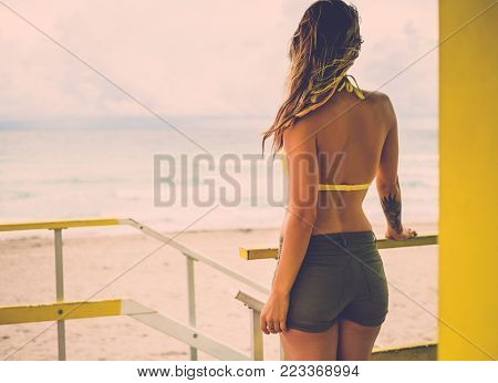 Beautiful woman in bikini at the lifeguard station, Miami, USA.