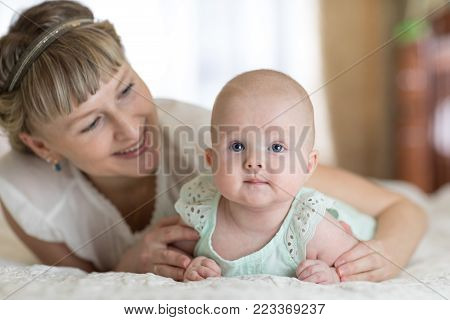 Mom and her small daughter lying down on bed in nursery room. Mother embracing infant baby.