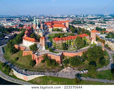 Poland. Skyline panorama of Cracow old city with Wawel Hill,  Cathedral, Royal Wawel Castle, defensive walls, park, promenade and unrecognizable walking people.
