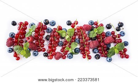 Mix berries isolated on a white. Ripe blueberries, red currants, black currant and raspberries. Berries and fruits with copy space for text. Various fresh summer berries on white background. Background berries. Top view.
