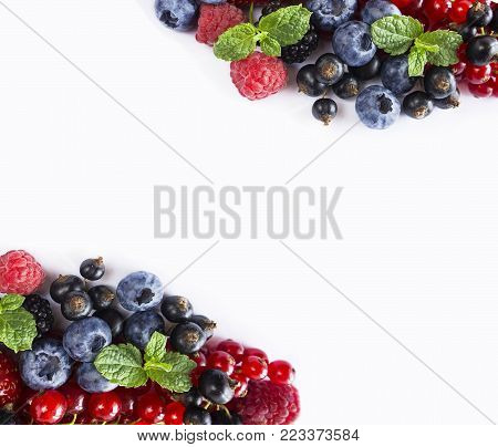 Mix berries isolated on a white. Berries and fruits with copy space for text. Ripe blueberries, blackberries, red currants, black currant, raspberries and strawberries. Various fresh summer berries on white background. Background berries.