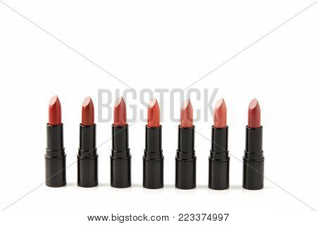 row of red lipsticks of various shades isolated on white