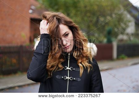 sad lonely depressed young woman ruffling her hair outdoors on suburban street in Germany