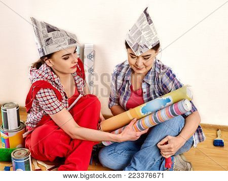 Repair home women holding bank with paint for wallpaper. Elderly mother and daughter renovation apartment . House renovation. Friendly family relationships.