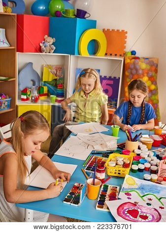 Small students painting in art school class. Child drawing by paints on table. Girls in kindergarten. Drawing education develops creative abilities of children. Best hobbies children's club.