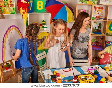 Children painting finger on easel. Group of kids girl and boy with teacher learn paint in class school. Child picture on background. Students kids draw rainbow.