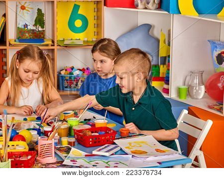 Small students painting in art school class. Child drawing by paints on table. Boy and girls in kindergarten. Drawing education develops creative abilities of children. Best home children's club