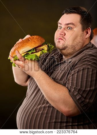 Man eating fast food hamberger. Fat person made great huge hamburger and admires him, intending to eat it. Junk meal leads to obesity. Person regularly overeats concept .