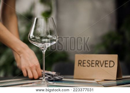 Hands of unrecognizable waiter serving tableware on reserved table in restaurant.