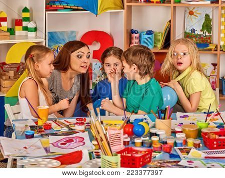Kids playroom organization of children painting and drawing in kid's club. Craft lesson in primary school. Kindergarten teacher and students work together. Animator entertains children.