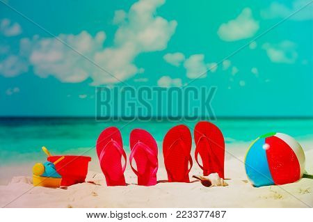 flip-flops, toys and shell at tropical beach, family vacation