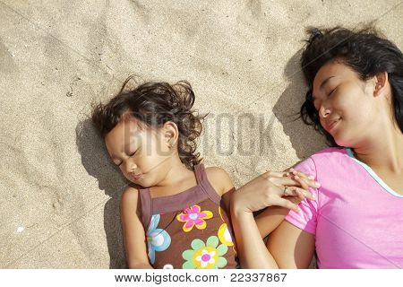 Mother And Child Lie Down On The Beach Sand