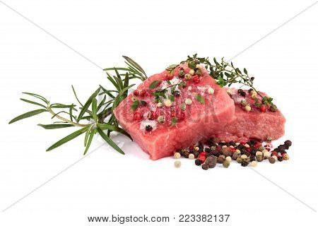 Fresh raw beef meat slices with color peppercorn and rosemary isolated over white background