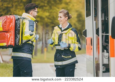 Paramedic nurse and emergency doctor at ambulance with kit