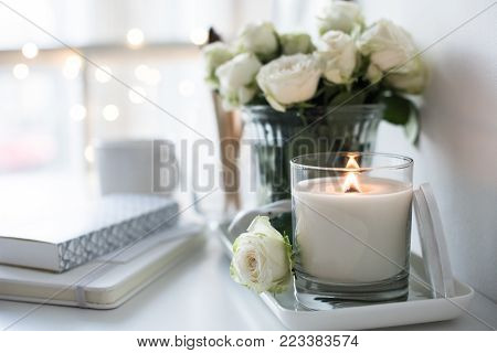 White room interior decor with burning hand-made candle and bouquet of fresh roses on table, luxury home decorations in daylight closeup