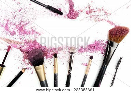 Traces of vibrant pink powder and blush forming a frame, with makeup brushes and lip gloss. A template for a makeup artist's business card or flyer design, with copy space
