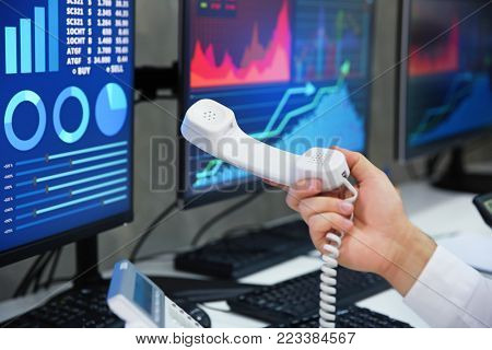 Male stock trader holding telephone receiver in office