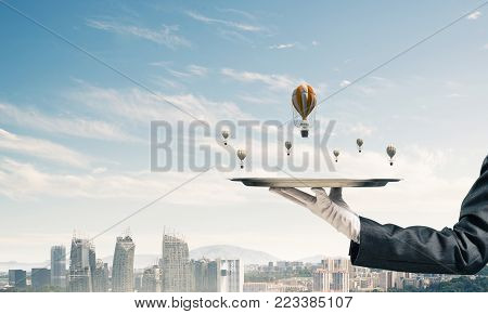 Closeup of waitress's hand in glove presenting flying aerostats on metal tray with modern cityscape view on background. 3D rendering.