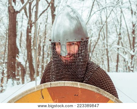 Medieval viking warrior in chain mail and helmet holds a shield in the winter forest