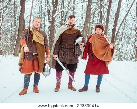 Group of armed medieval warriors with shields, swords, spears in the winter forest