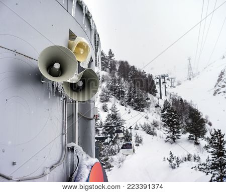 Three speakers installed on wall of the building for information news and warnings in the mountains in the winter resort. Cableway in the mountains