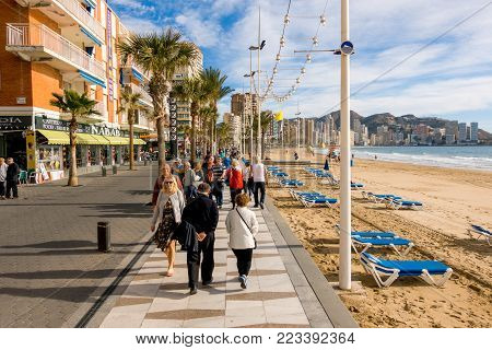 BENIDORM, SPAIN, DECEMBER 14, 2017: People walking on the embankment of Benidorm, Spain