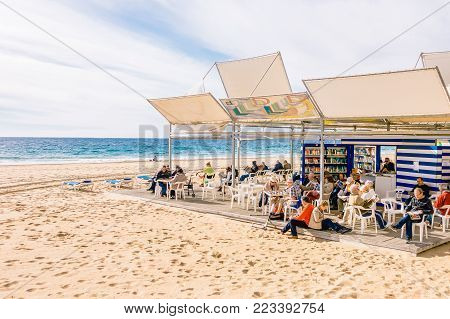 Benidorm, Spain - January 14, 2018: People resting, reading and playing chess resting in public Benidorm Levante Beach Library
