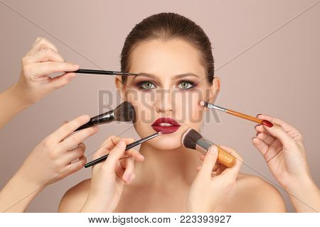 Professional visage artists applying makeup on woman's face on light background