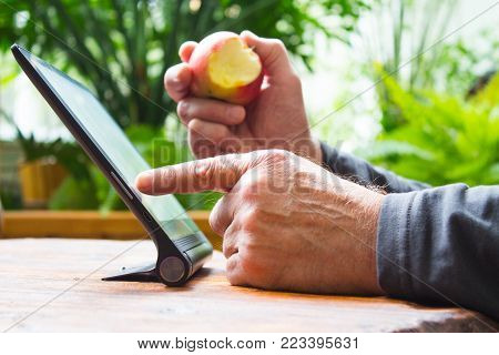 Man working on tablet computer with bitten apple in his hand. Wooden table. Green garden background.