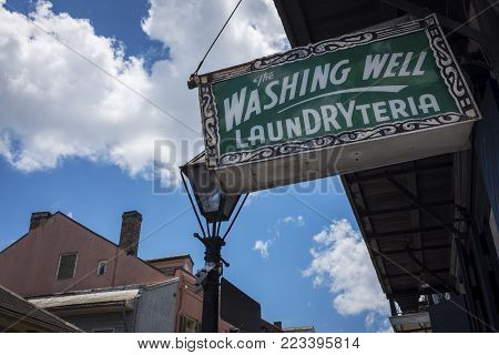 New Orleans, Louisiana - June 18, 2014: An old and rusty billboard for a laundry store in the French Quarter in New Orleans, Louisiana, USA.