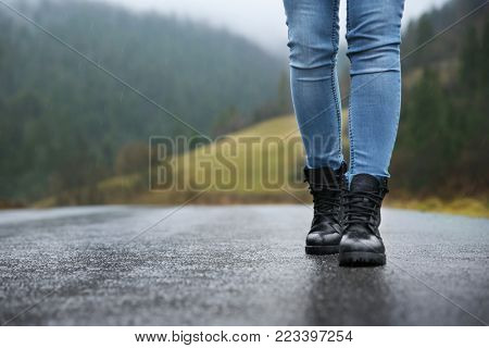 Female tourist walking along countryside road in the rain