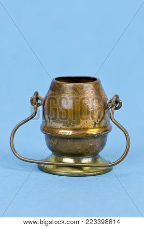 Decorative brass copper pot with handle on azure blue bacground