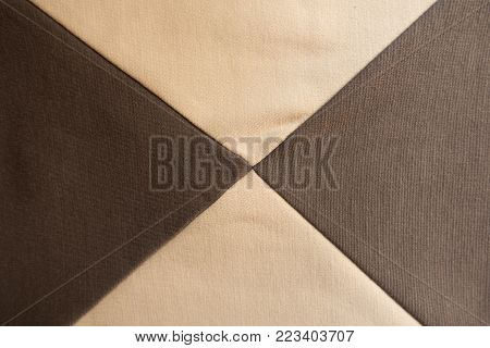 Four gores of beige and brown fabrics sewn together