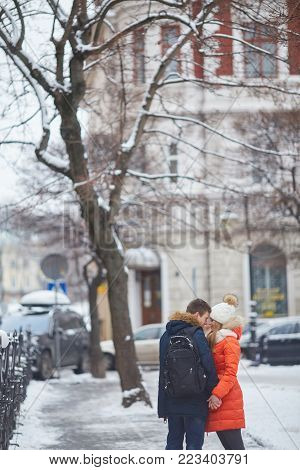 Young couple kissing at wintertime outdoors doing christmas shopping.