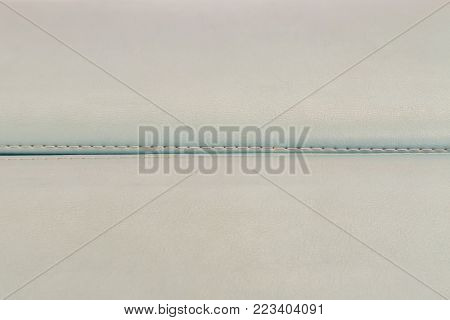 light blue leather background with stitches in the middle