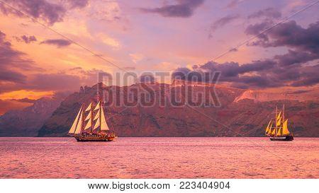 Sailboat in Santorini, Greece. Sailing ship navigate near an island in Cyclades. The photo is taken at sunset.