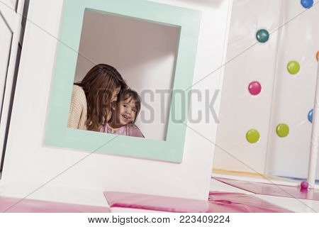 Mother and daughter playing in a playroom, hiding in a small wooden house, whispering and storytelling