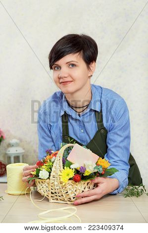Smiling young female florist working in flower shop. Portrait of beautiful caucasian girl self-employed in flower shop, smiling and looking at camera.