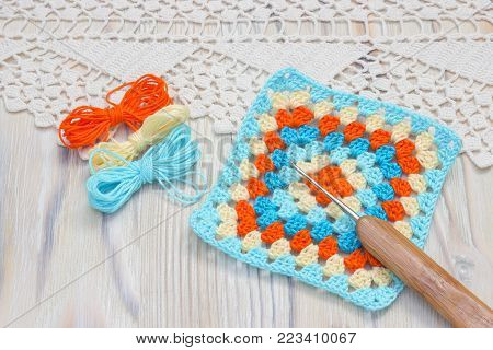 The beginning of bright plaid, blanket. Homemade creative crochet pattern. Crochet handmade granny square and yarn balls. Colorful original knitted handmade work. Crochet stitches. Rustic background