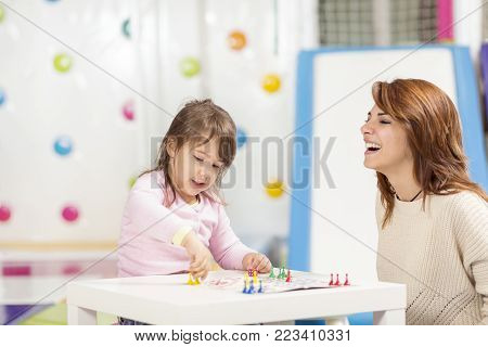 Mother and daughter sitting in a playroom, playing a ludo game and enjoying their time together. Focus on the daughter