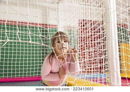 Cheerful child playing on a trampoline in a playroom