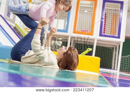 Beautiful mother and daughter playing in a playroom, mother lying on the floor and lifting daughter. Focus on the daughter