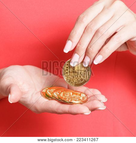 ICO and Token Sale concept - Initial Coin Offering in the female hands. The woman in a red blouse holds a gold crypto coin in hand.