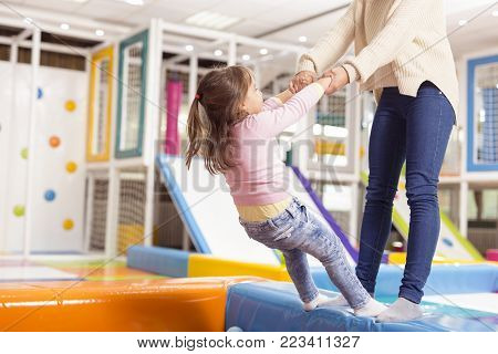 Mother and daughter playing in a playroom, standing on the edge of the colorful ball pool, getting ready to jump