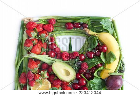 Weighing scales made from fruits and vegetables over a white background