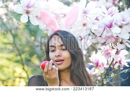 egg in hand of happy woman or adorable girl with sexy, plush lips and rosy bunny ears on long, brunette hair at blossoming, magnolia flowers, trees, garden on floral background. Easter. Spring