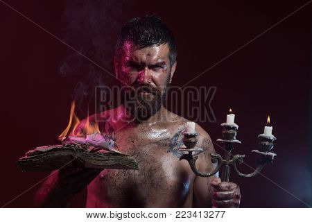 Halloween holidays celebration. Hipster man with book and candles burning on purple background. Magic spell, enchantment, witchcraft. Wizard, sorcerer, warlock. Might, mystic, knowledge.